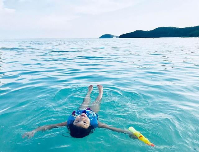 Cô nhóc còn nằm ngửa trên mặt biển để mẹ chụp hình.