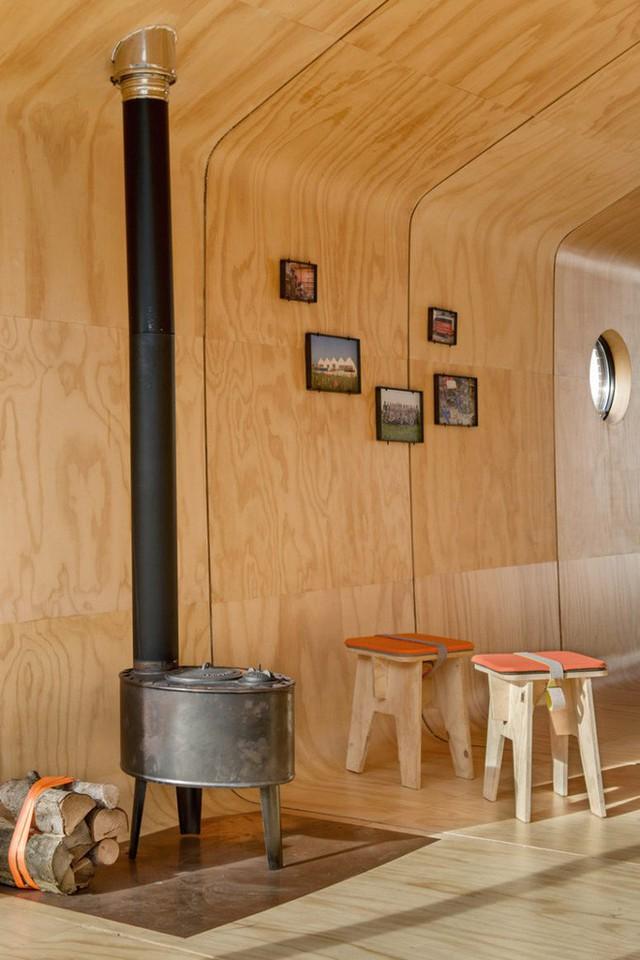 Không gian nhỏ nhưng vẫn có đầy đủ đồ dùng từ bàn ghế, giường, kệ, ti vi đến lò sưởi.