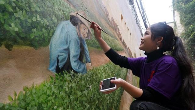 Một nữ họa sĩ đang thi công tác phẩm làng Láng của mình trên nền tường cũ kỹ.