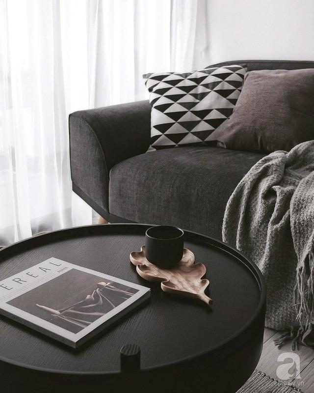 Chiếc bàn trà màu đen ấn tượng, tạo sự liên kết sắc màu ăn ý với khung tranh trên tường và công tắc điện.