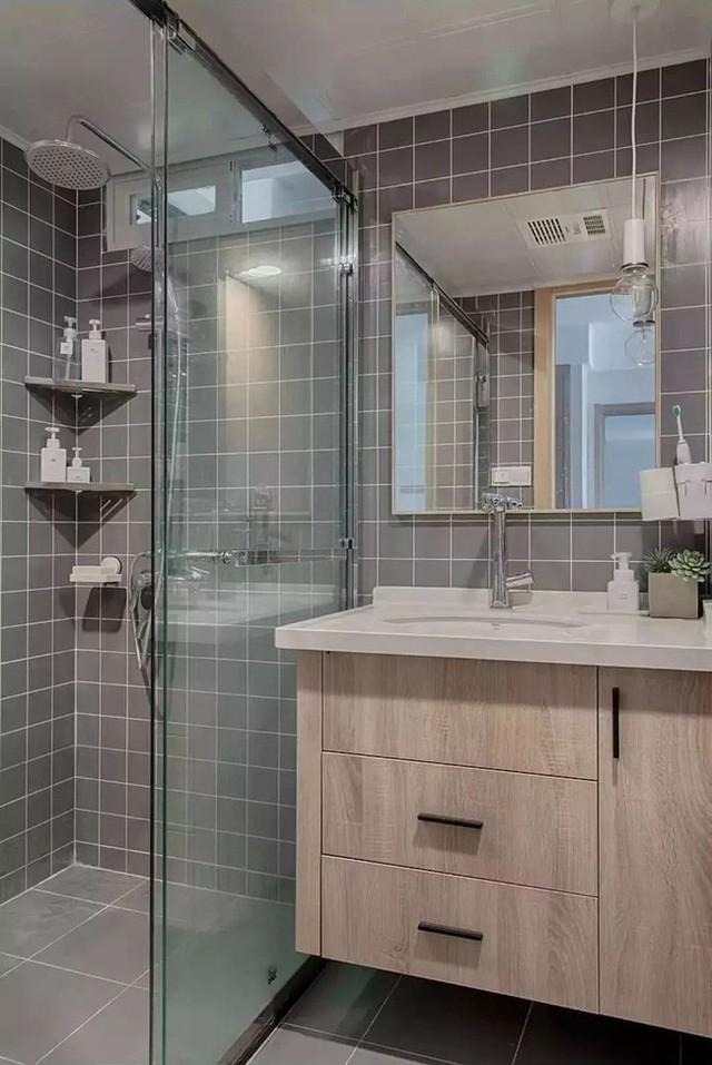 Bức tường của phòng tắm ứng dụng thiết kế gạch nhỏ hiện đại, tủ lưu trữ lớn và tấm kính trong suốt ngăn cách giúp ăn gian diện tích phòng.