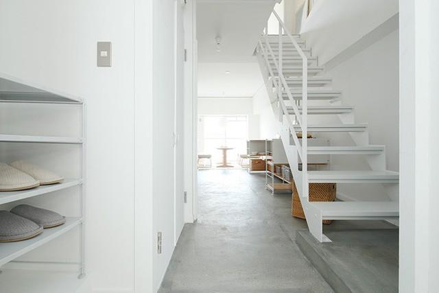 Lối vào nhà được gia chủ bố trí kệ đựng giày dép, vị trí đặt cầu thang lên xuống và hệ thống tủ đựng đồ ăm tường. Còn lại là lối đi và tạo sự thoáng đãng cho không gian.