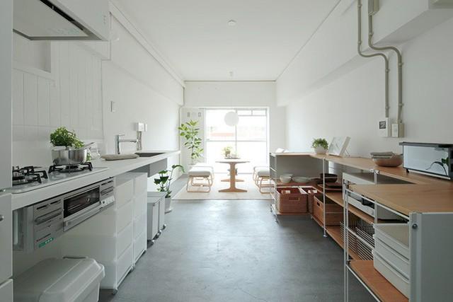 Tiếp nối phía sau cầu thang là hệ thống bếp nấu hiện đại và kệ đựng đồ sát tường. Vì diện tích khá hạn hẹp nên mọi vật dụng và hệ thống nấu nướng đều được bố trí song song.