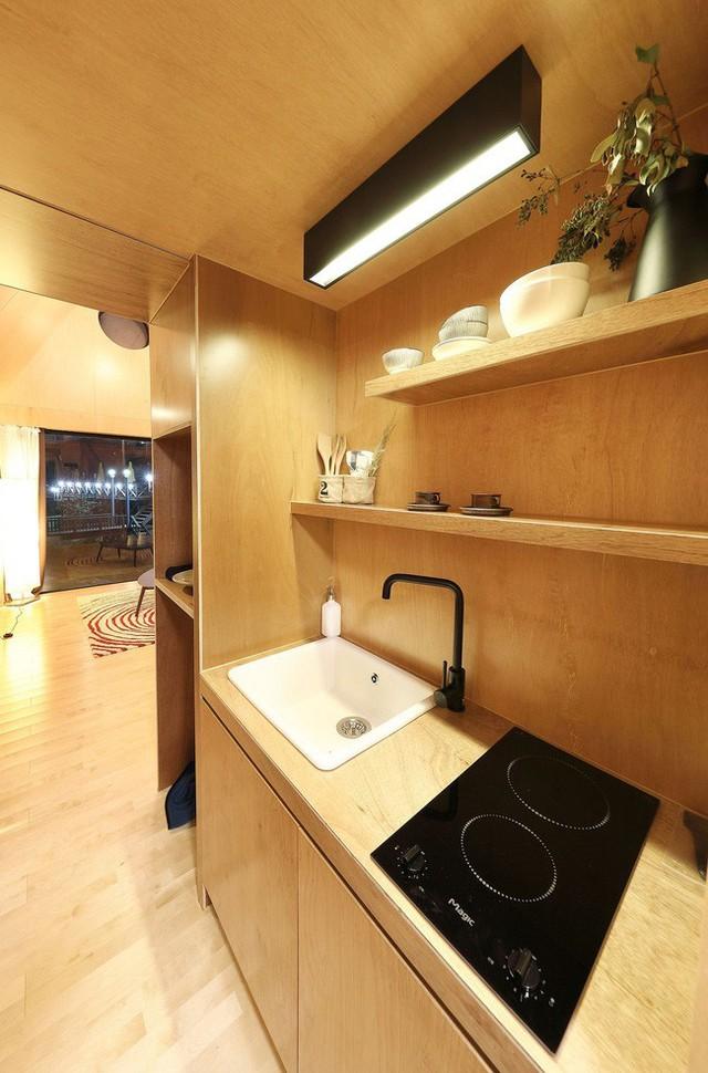 Nhà bếp của ngôi nhà nhỏ với kệ gỗ và tủ thông minh.