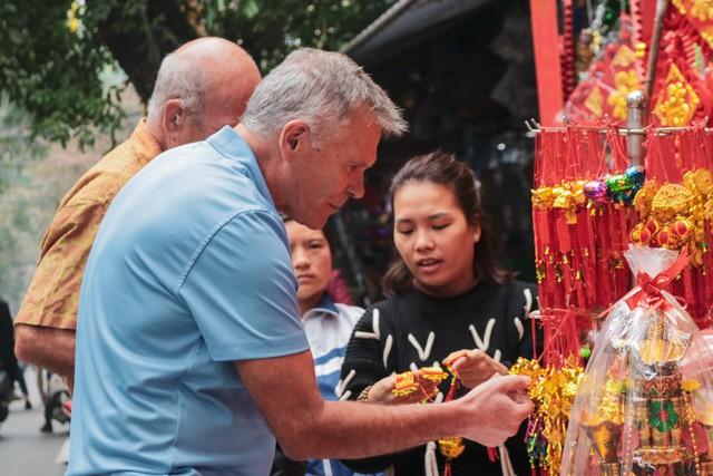 Ngoài việc chụp ảnh, nhiều người ngoại quốc cũng hứng thú với những vật trang trí trong Tết cổ truyền của Việt Nam.