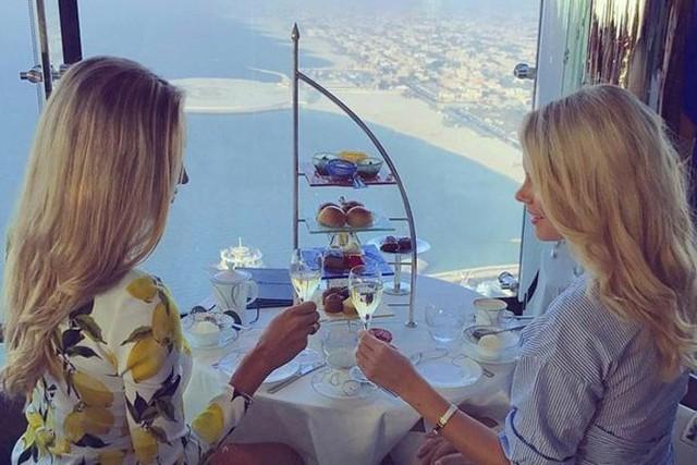 Hai tiểu thư hội con nhà giàu Dubai thưởng thức bữa sáng trong một nhà hàng trên tòa nhà chọc trời. Dubai có nhiều tòa nhà hiện đại và những khu nghỉ dưỡng đắt đỏ, là sân chơi hoàn hảo dành cho những người giàu có.
