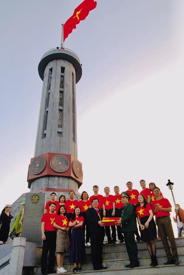 Thượng tá Phạm Ngọc Thủy, Chính trị viên đồn biên phòng Lũng Cú trao tặng lá cờ Tổ quốc cho một đoàn khách ngay tại chân cột cờ Quốc gia.