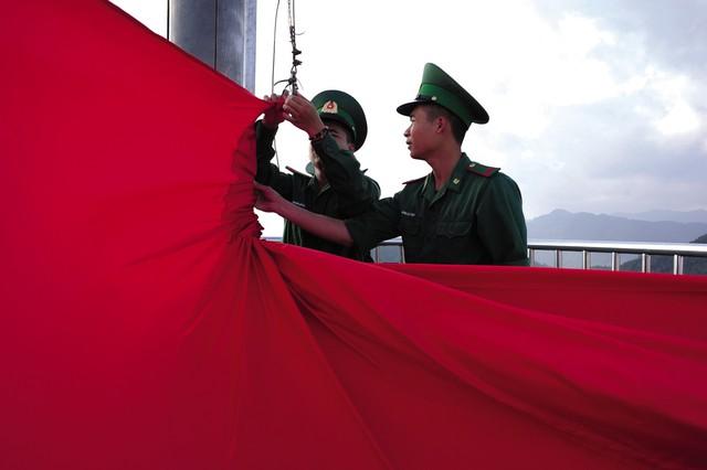 Hai Binh nhất Nông Văn Thiếp và Đoàn Văn Chuyên hạ lá cờ số 395 để thay lá cờ mới. Một trong những nhiệm vụ quan trọng hàng đầu của các chiến sĩ đồn biên phòng Lũng Cú là kiểm tra, bảo vệ và gìn giữ cho lá cờ luôn được tung bay với trạng thái hoàn hảo nhất.