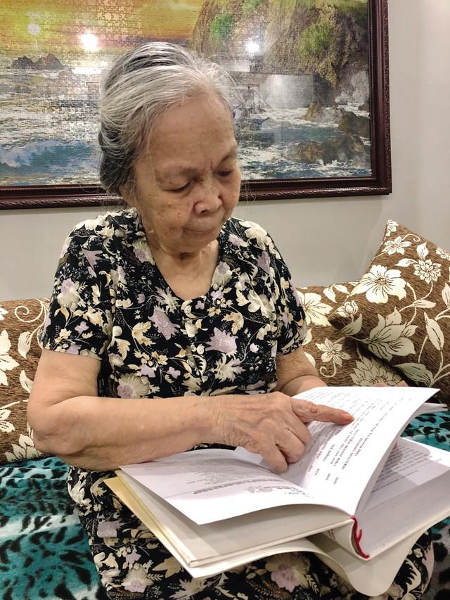 Bà Hoàng Thị Liên bên tác phẩm nghiên cứu về cuộc đời của GS Tạ Quang Bửu. Ảnh: TH