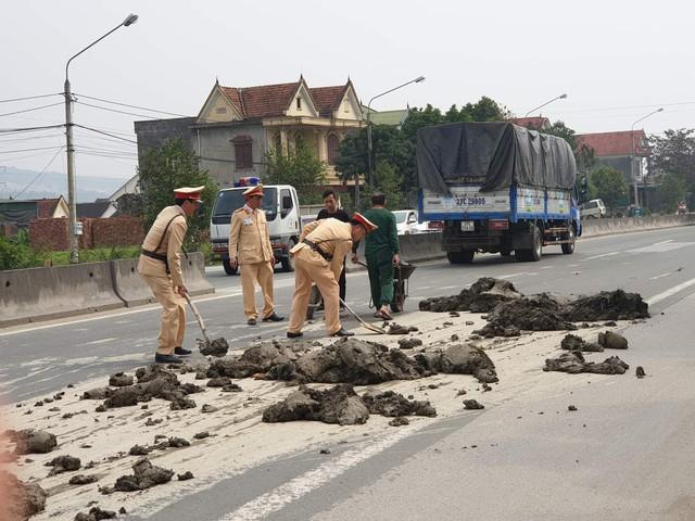 Hình ảnh các chiến sỹ CSGT dọn dẹp đất bùn rơi vãi ra đường được người dân ghi lại.