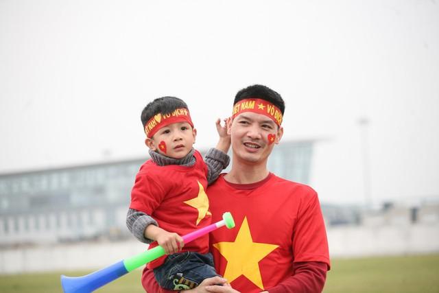 Hai cha con khoác lên mình lá cờ đỏ sao vàng và kèn để ủng hộ đội tuyển.