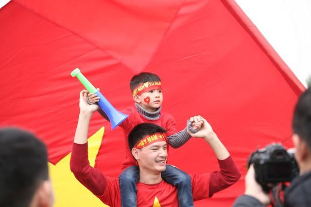 Hai cha con cháy hết mình cùng ủng hộ các cầu thủ chuẩn bị xuống sân bay.