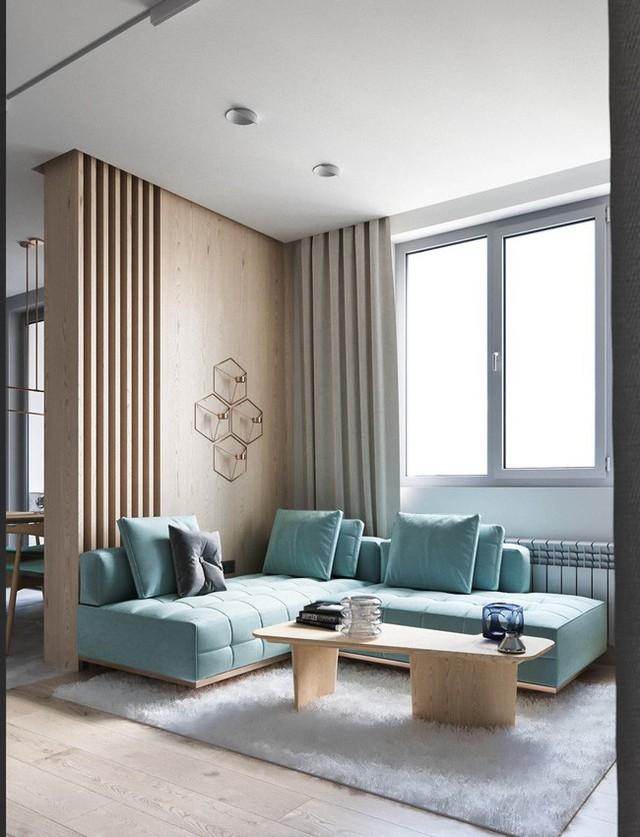 Chiếc ghế sofa màu xanh dương pastel chiếm toàn bộ diện tích phòng khách được đặt trên một thảm lông mềm mại và ấm áp rất sang chảnh.