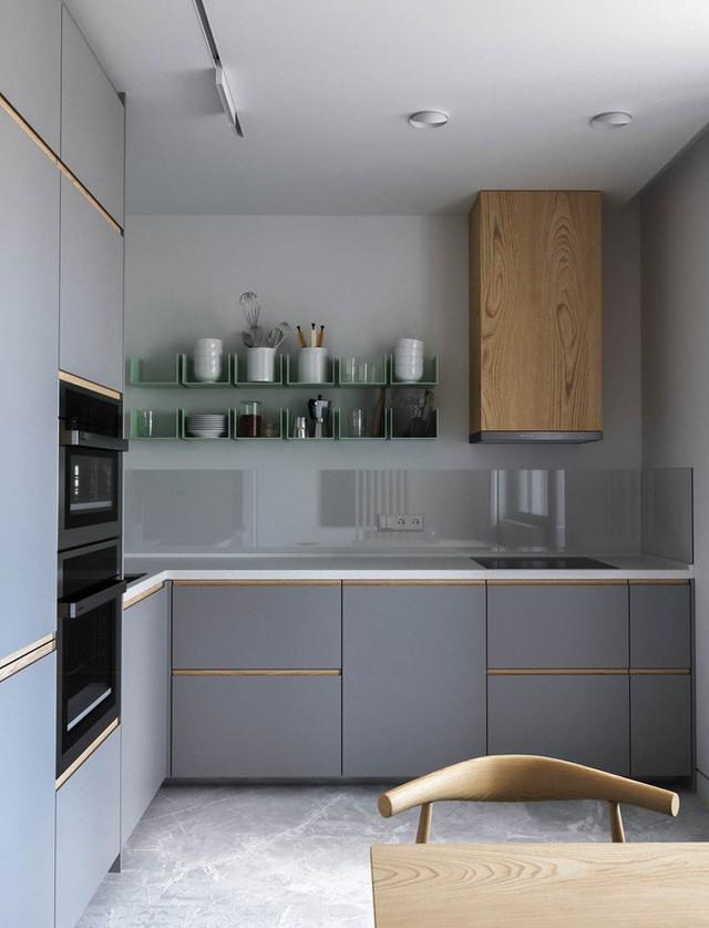 Tủ đựng và kệ bếp được sử dụng từ chất liệu gỗ tối màu cho khu vực ăn uống có diện tích hơi nhỏ.