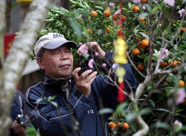 Một cụ già dù mắt đã kém nhưng vẫn cố gắng nhíu mày để tự tay chụp lại bức ảnh kỷ niệm về chợ hoa Hàng Lược.
