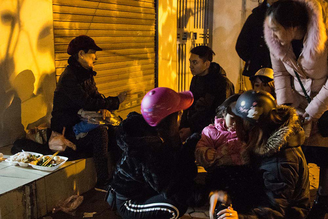 Hai bà cháu vô gia cư đang ngồi ăn trước hiên nhà gần khu vực công viên Thống Nhất.