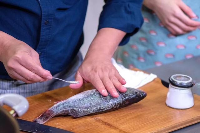 - Cầm đầu cá, nhúng thân cá vào một nồi nước sôi trong 3 giây sau đó cho cá vào ngay bát nước lạnh để tránh cá bị nát. Tương tự, cầm đuôi cá rồi nhúng đầu cá vào nồi nước sôi trong 3 giây, sau đó nhúng đầu cá vào bát nước lạnh. Điều này giúp loại bỏ bớt chất nhớt ở cá.