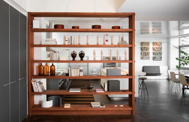 Một tủ sách bằng gỗ kiểu dáng đẹp mắt không che chắn mặt sau giúp phân chia khu vực sinh hoạt theo hướng mở rộng mà không cản ánh sáng mặt trời chiếu vào phòng.