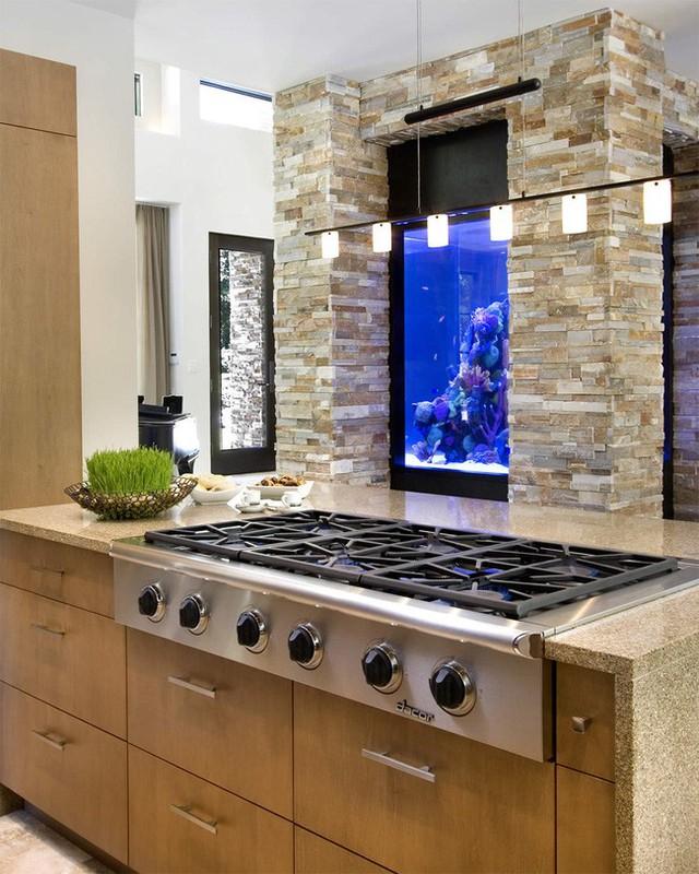 1. Một bể cá cỡ lớn được lồng ghép trong hai thanh trụ nhà và nằm trên một bếp đun trong không gian phòng ăn. Một dàn các loại đèn chiếu sáng được sử dụng để các chú cá thêm lung linh, huyền ảo.