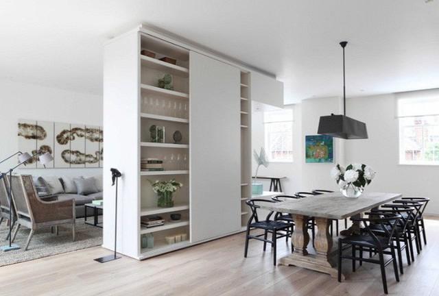 Một tủ đặt ở trung tâm nhà với diện tích khá lớn có thể lưu trữ dao kéo và đồ sứ cho phòng ăn, giữ sách và tivi ở phía phòng khách.