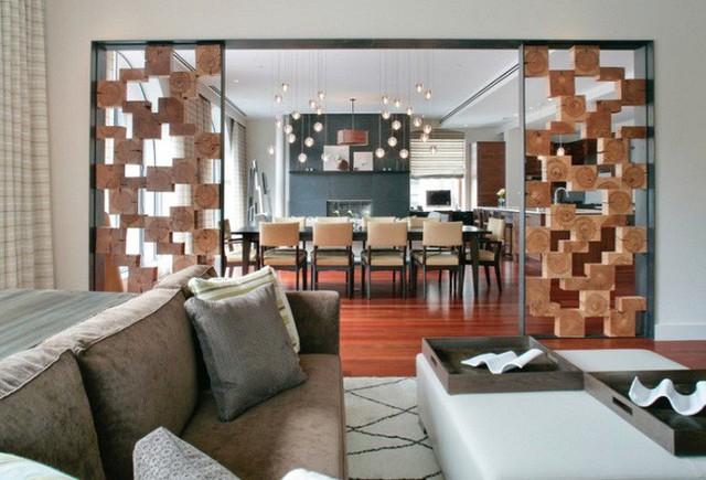 Các tấm gỗ xếp chồng lên nhau tạo thêm hình ảnh đồ họa cho vách ngăn phân chia phòng khách và phòng ăn.