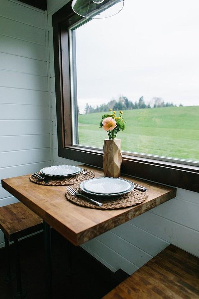Khu vực ăn uống nhỏ và xinh bên cạnh cửa sổ có ghế gỗ cho hai người.