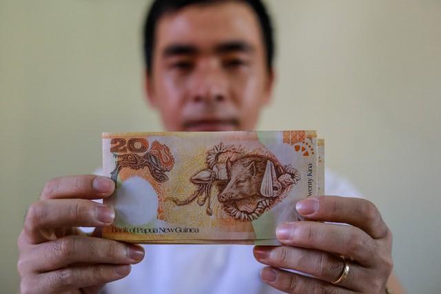 """Anh Tiệp cầm tờ tiền 20 Kina của Papua New Guinea có giá bán 50.000 đồng mỗi tờ. Tờ tiền này được phát hành để kỷ niệm 35 năm ngày thành lập Ngân hàng Papua New Guinea năm 2008. """"Điều đặc biệt là mặt sau tờ tiền in hình chú heo rừng với những hình vẽ ấn tượng bao quanh – biểu tượng của văn hóa địa phương, hình ảnh này mang đến sự may mắn, sức khỏe và tài lộc"""", anh lý giải."""