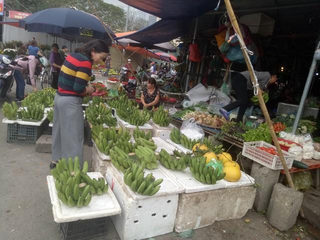 Người dân chọn mua chuối xanh để bày mâm ngũ quả ở chợ Nam Trung Yên (Hà Nội). Ảnh: Thiên Hương