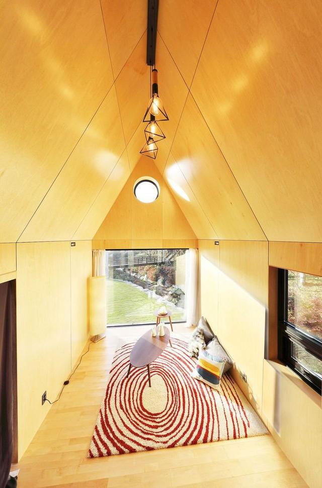 Bước vào bên trong, đầu tiên bạn thấy là phòng khách. Bạn có cảm giác căn phòng rộng rãi hơn rất nhiều so với thực tế nhờ việc không có các món đồ trang trí và mái nhà dốc làm tăng chiều cao cho ngôi nhà.