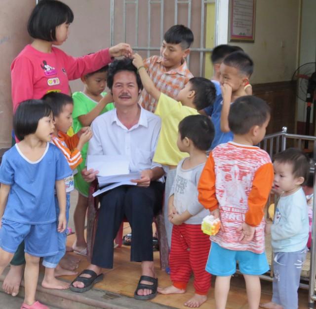 Các trẻ vui đùa bên thầy Lê Trung Thực.