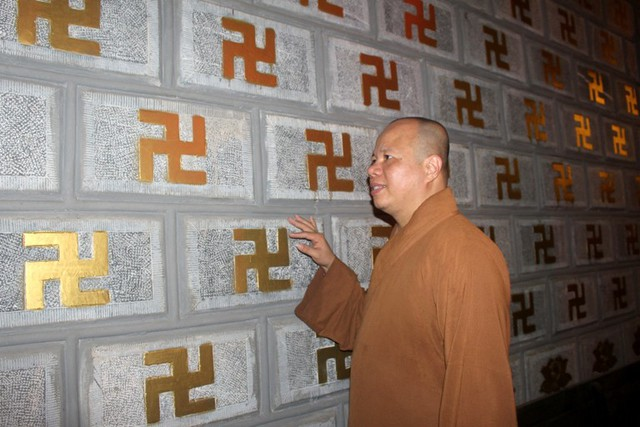 Thượng tọa Thích Thanh Cường - Trụ trì chùa Cương Xá bên bức tường đá khắc chữ Vạn. Ảnh: Đ.Tùy