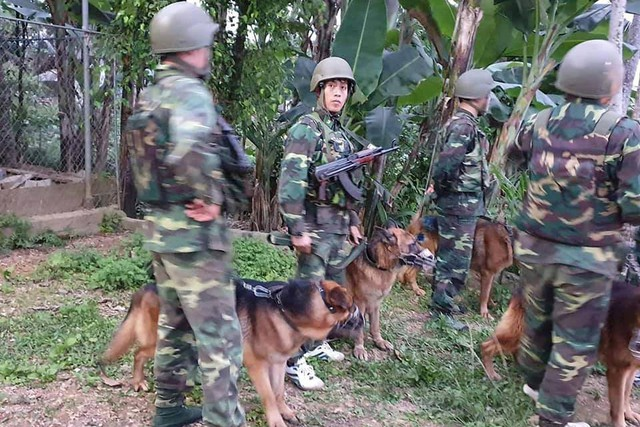 Lực lượng cảnh sát cùng chó nghiệp vụ truy bắt tên bỏ trốn.