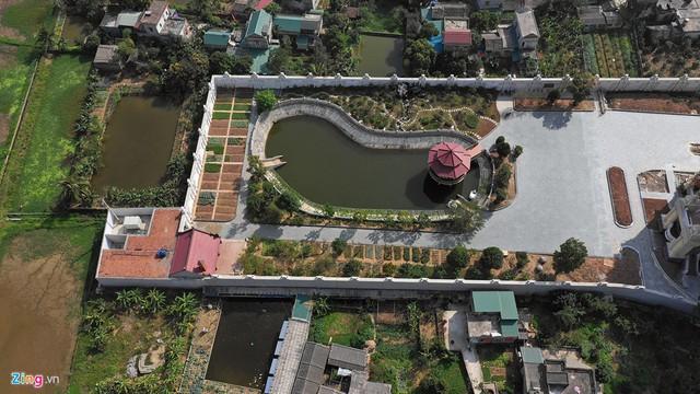 Phía sau là hồ nước lớn, xung quanh như một công viên, bên ngoài có tường bao.