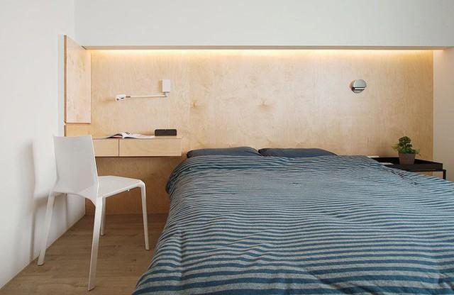 Góc đặt giường ngủ gọn gàng và ấm cúng với ánh sáng LED màu vàng.