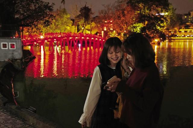 Hai cô gái trẻ xem lại ảnh họ vừa chụp trên điện thoại di động, bên cạnh cầu Thê Húc dẫn ra đền Ngọc Sơn - di tích quốc gia đặc biệt của Việt Nam, một trong những biểu tượng của Thủ đô Hà Nội.