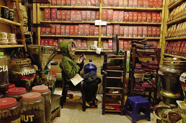 Cô gái ngồi bên trong một cửa hàng bán cà phê xay và cà phê hạt ở Hà Nội.