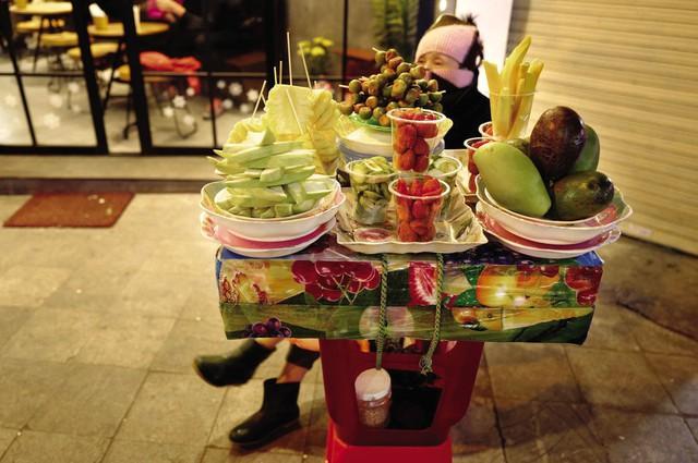 Những khay hoa quả gọt sẵn được bày bán đơn giản với chỉ vài chiếc ghế nhựa và bàn gỗ gần hồ Hoàn Kiếm.