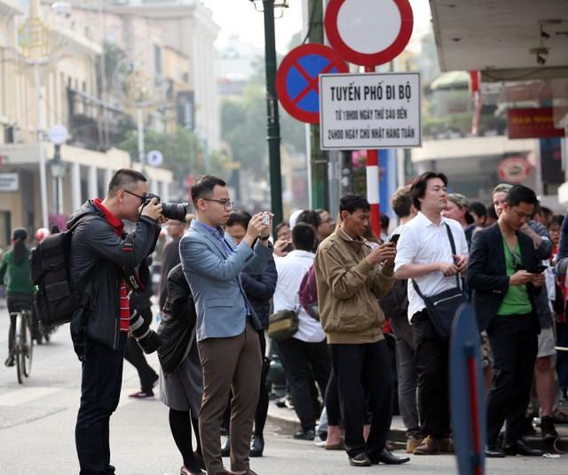 Nhiều người đi đường hiếu kỳ chụp ảnh.