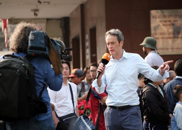 Một nam phóng viên dẫn hiện trường trên đường.