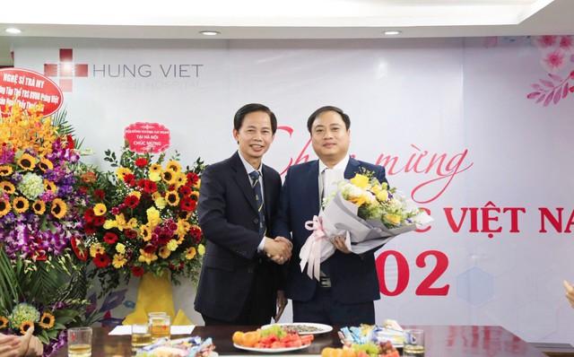 Chủ tịch HĐQT Vũ Hoàng Nguyên (phải) tặng hoa, chúc mừng ông Nguyễn Đức Văn- Giám đốc nhân sự của bệnh viện
