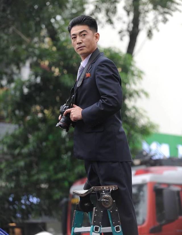 Phóng viên ảnh mang theo thang để tác nghiệp nhưng vẫn tuân thủ về trang phục. Ảnh: Hoàng Chí Hùng