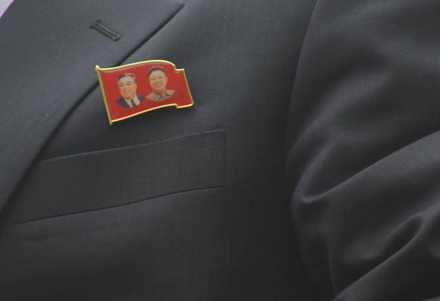 Phù hiệu có hình ảnh của hai nhà lãnh đạo Kim Nhật Thành và Kim Jong-il được gắn trên áo của các phóng viên. Ảnh: Hoàng Chí Hùng