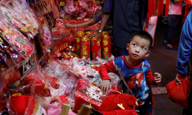 Bé trai đứng tại quầy hàng trong khu chợ truyền thống tại thủ đô Jakarta, Indonesia.