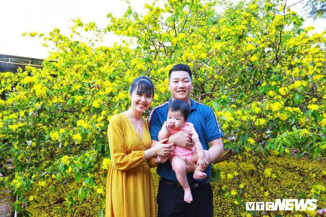 Một gia đình nhỏ chụp hình kỷ niêm bên cây mai.