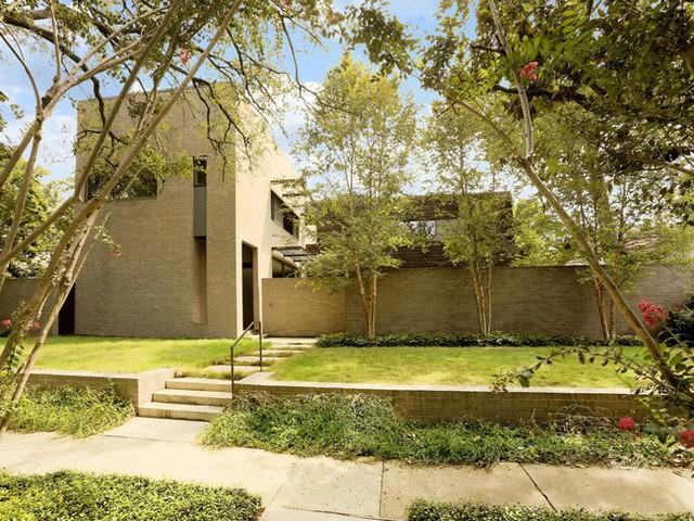 Bên ngoài ngôi nhà rợp bóng cây và những thảm cỏ xanh mướt. Chất liệu gạch được sử dụng cho toàn bộ tường, hàng rào và lối đi của ngôi nhà.