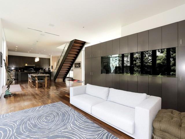 Tiến vào bên trong, không gian cởi mở và thoáng đãng nhờ vào nội thất hiện đại. Ở đây, bạn có thể thấy điểm nhấn là một chiếc tủ lớn kết hợp với bể cá được đặt phía sau ghế sofa.