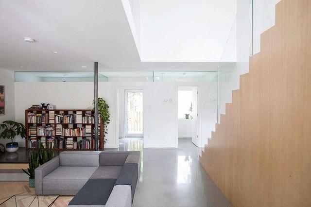 Với phong cách Scandinavian đến từ Bắc Âu thì tường nhà được sơn màu trắng tinh theo đúng công thức. Một cầu thang bằng gỗ với lan can được làm từ thủy tinh để nối liền giữa hai tầng lầu.