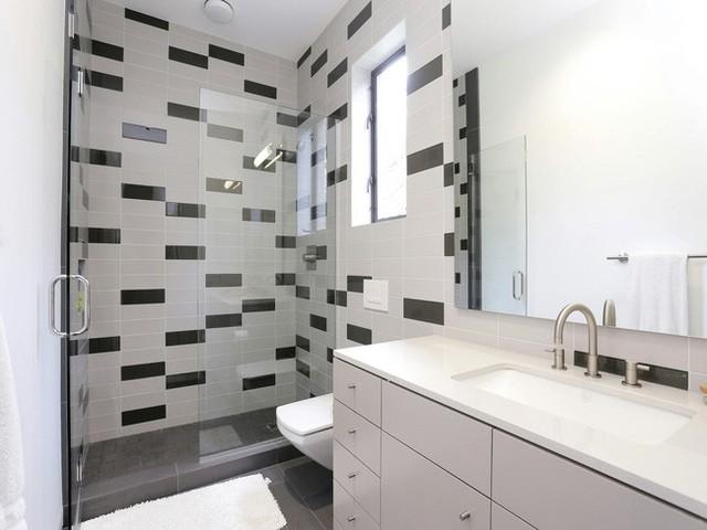 Cả ngôi nhà có tận 6 phòng tắm với nhiều thiết kế khác nhau. Ở phòng tắm này khu vệ sinh và nhà tắm được ngăn đôi và được sử dụng hai màu gạch đen trắng để trang trí.