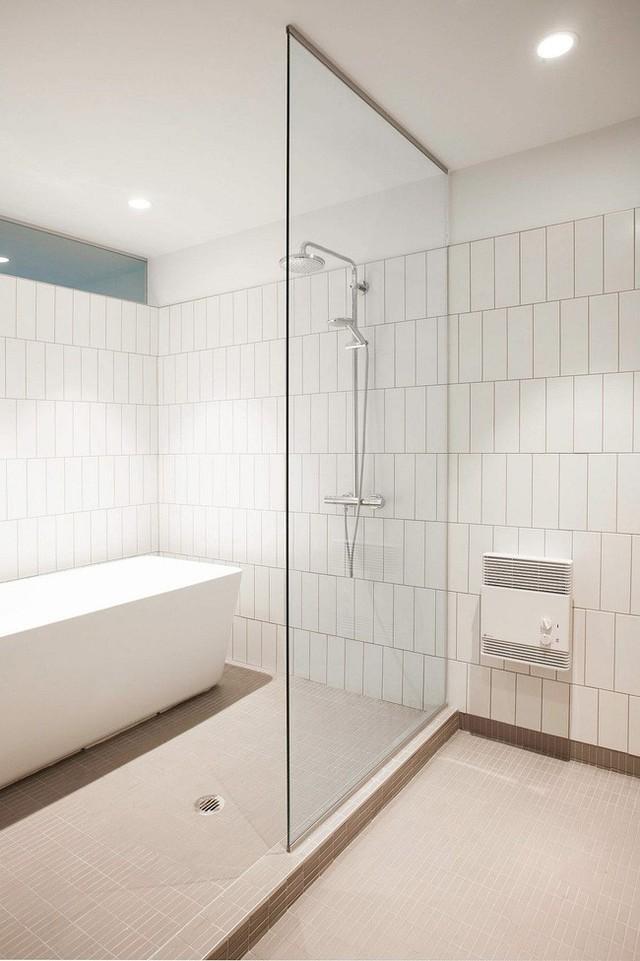 Nhà tắm cũng được thiết kế đơn giản với một vách ngăn bằng thủy tinh trong suốt, bồn tắm đơn màu trắng và tường được lát bằng gạch men.