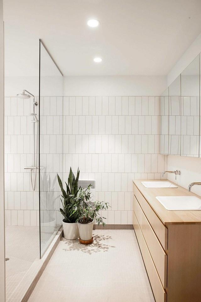 Hai chậu cây xanh cỡ lớn được đặt ngay bên cửa kính giúp không gian phòng tắm thêm xanh tươi.